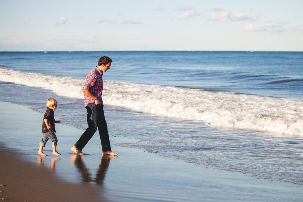 Bonding between children and parents -  A Dad and child at the beach sharing each other's company
