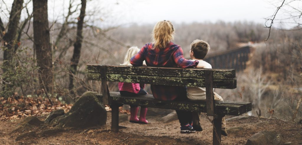 Bonding between children and parents - A Mother with her kids at a park bench enjoying nature